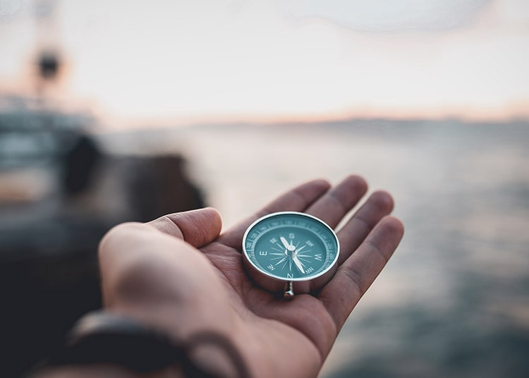 Hand with compass on blurred background