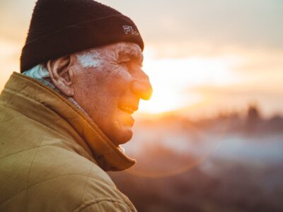 An older man standing outside at sunset