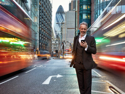 Man in suit holding a phone standing on a busy London street