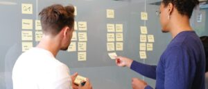 Two people working with post-it notes