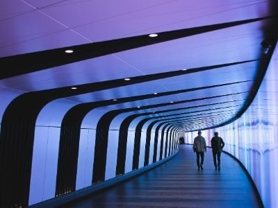 Two people walking through futuristic corridor